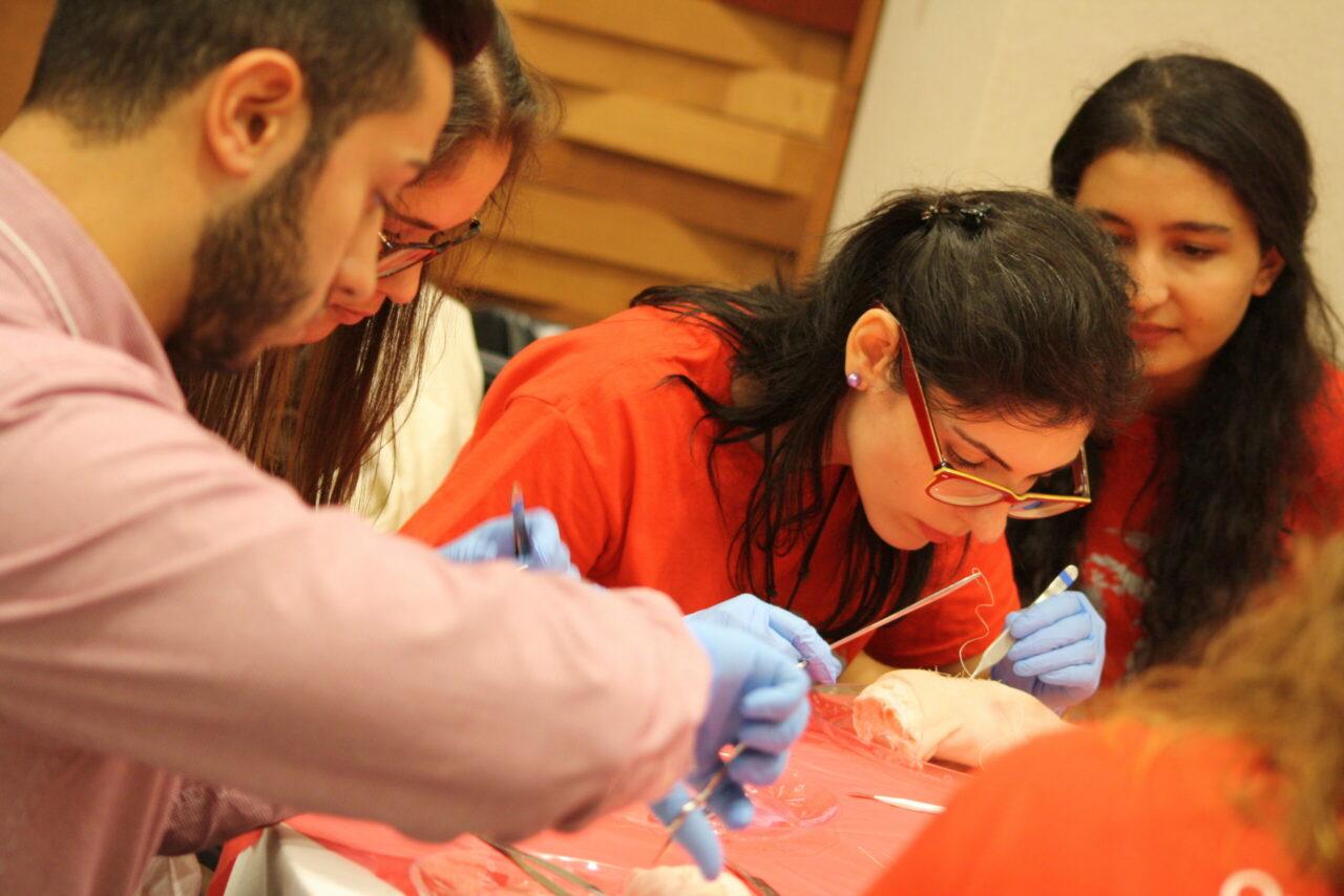 Étudiante pratique ses compétences de suture sur le pied d'un cochon. (Photo: Annelise Miller)