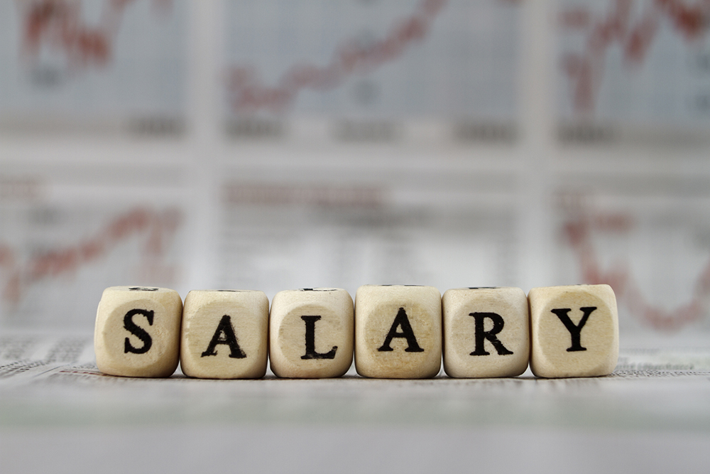 Salary word built with letter cubes on newspaper background